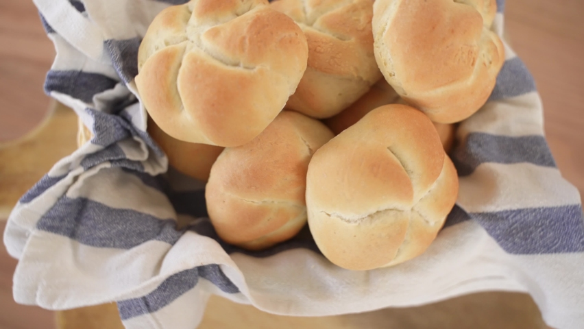 Freshly Baked Kaiser Rolls in Woven Basket on Wooden Background, Top Down View | Shutterstock HD Video #1070791072