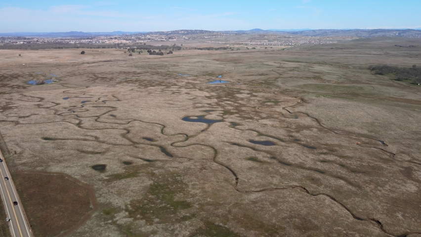 Realtime drone footage over Prairie City country park, California, USA, showing wide open scrubland countryside and waterways, on a warm morning with blue sky | Shutterstock HD Video #1070791714