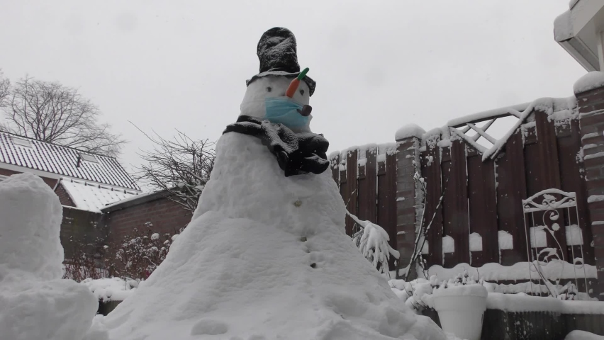 Snowman Wearing Protection Mask Standing Outdoors On A Snowy Winter Day - Covid Protection Concept - wide shot | Shutterstock HD Video #1070791831