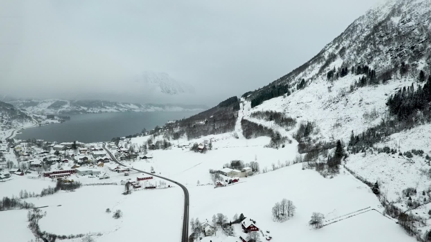 Drone shot of snowy mountains, Skei Village and natural lake in background during misty day in Norway. Aerial forward shot. Norwegian Travel resort in nature. | Shutterstock HD Video #1070792236