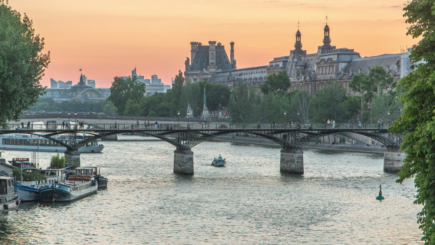 View to Pont des Arts in Paris after sunset day to night transition timelapse from Pont Neuf, France. Ship on the River Seine near square of the Vert-Galant. Reflection on water   Shutterstock HD Video #1070795020