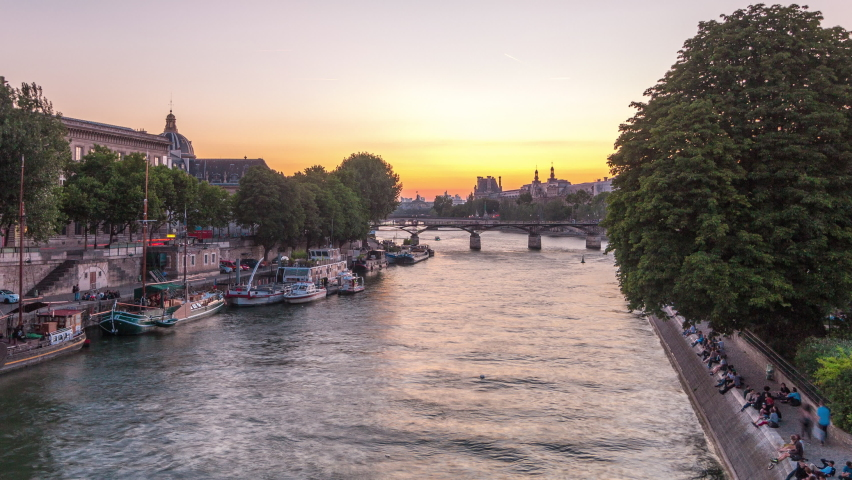 View to Pont des Arts in Paris after sunset day to night transition timelapse from Pont Neuf, France. Ship on the River Seine near square of the Vert-Galant. Reflection on water   Shutterstock HD Video #1070795095