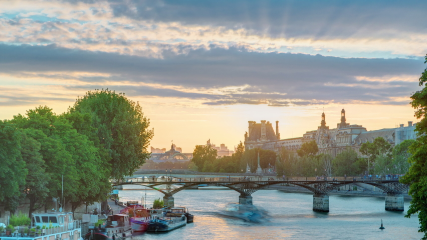 View to Pont des Arts in Paris at sunset timelapse from Pont Neuf, France. Ship on the River Seine near square of the Vert-Galant | Shutterstock HD Video #1070795212