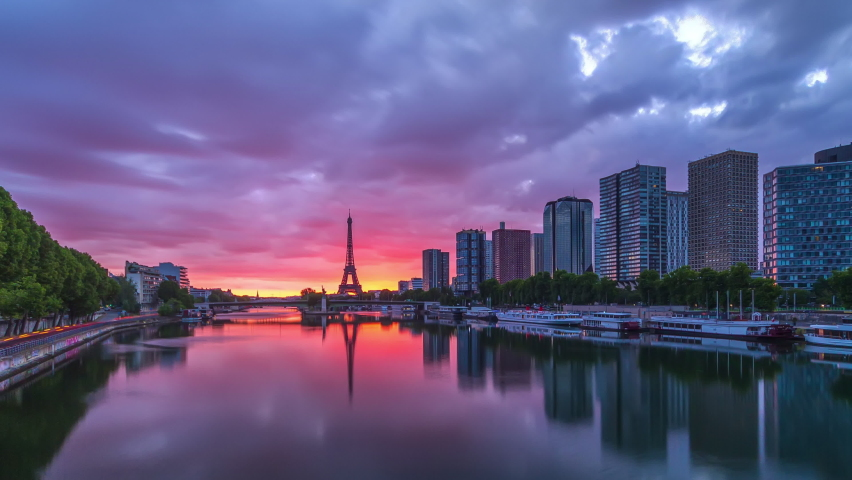 Eiffel Tower sunrise timelapse with boats on Seine river and in Paris, France. View from Mirabeau bridge. Modern buildings and traffic on a road. The Statue of Liberty | Shutterstock HD Video #1070795236