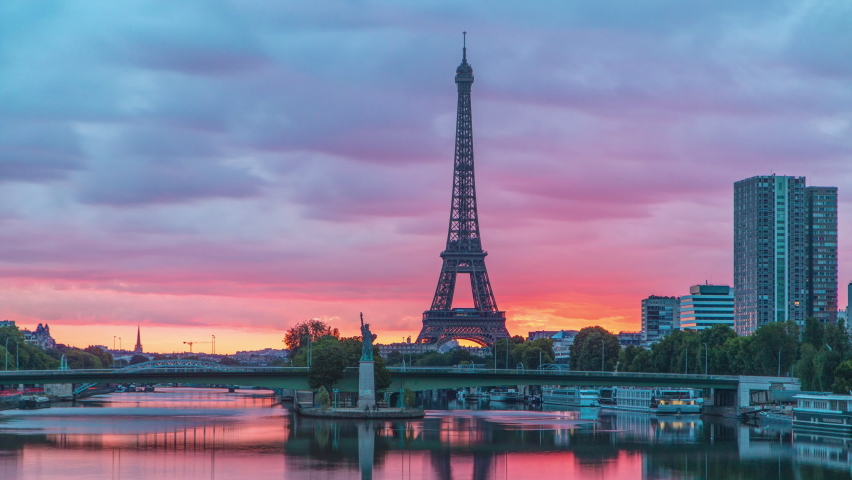 Eiffel Tower sunrise timelapse with boats on Seine river and in Paris, France. View from Mirabeau bridge. Modern buildings and The Statue of Liberty | Shutterstock HD Video #1070795248