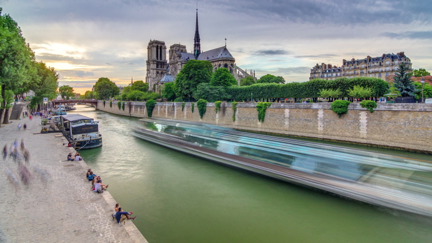 Sunset view of Cathedral Notre Dame de Paris timelapse in Paris, France. View from Bridge of the Archbishopric. Boat station and waterfront. Architecture and landmarks of Paris at summer day with | Shutterstock HD Video #1070795308