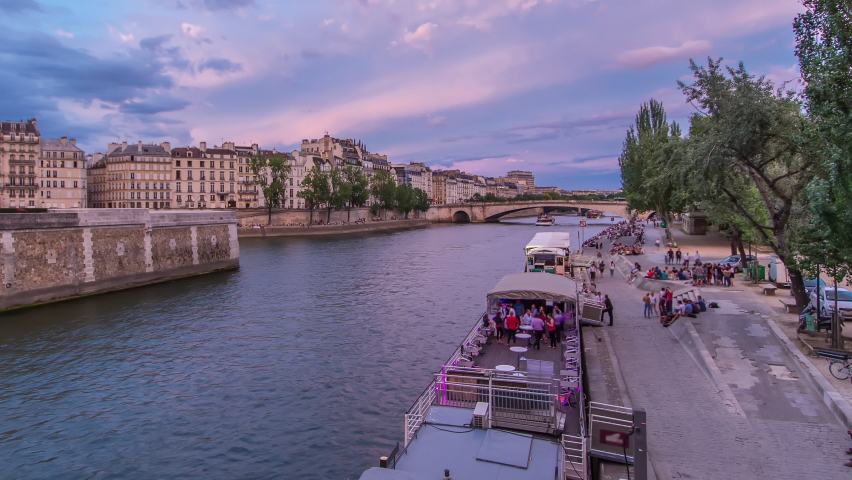 View to the Pont De La Tournelle on the River Seine day to night transition timelapse with waterfront from Bridge of the Archbishopric. Numerous such boats ply the Seine each day, passing many famous | Shutterstock HD Video #1070795335