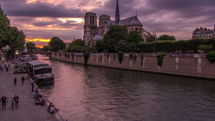 Cathedral Notre Dame de Paris day to night transition timelapse after sunset in Paris, France. View from Bridge of the Archbishopric. Boat station and waterfront. Architecture and landmarks of Paris | Shutterstock HD Video #1070795410