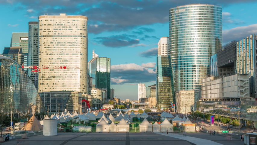 Modern skyscrapers during sunset timelapse in famous financial and business district of Paris - La Defense. Reflections on a glass with moving shasows at summer day. Arc de triomphe visible on the | Shutterstock HD Video #1070795416