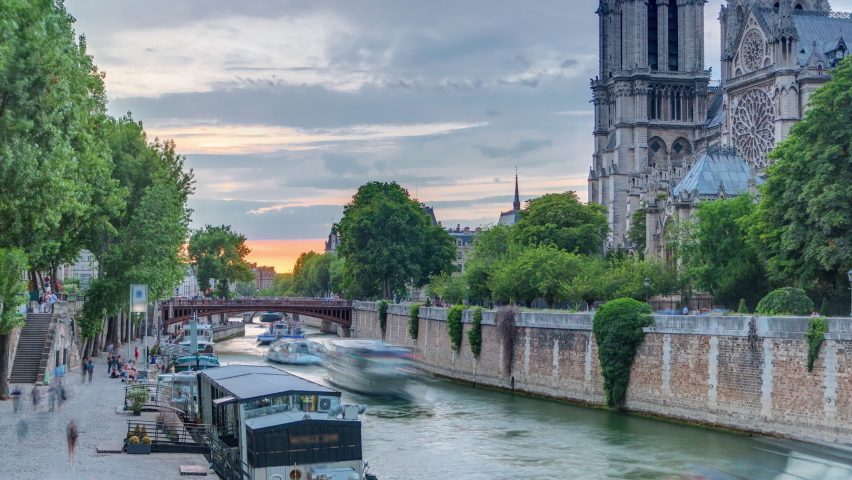 Sunset view of Cathedral Notre Dame de Paris timelapse in Paris, France. View from Bridge of the Archbishopric. Boat station and waterfront. Architecture and landmarks of Paris at summer day with | Shutterstock HD Video #1070795428