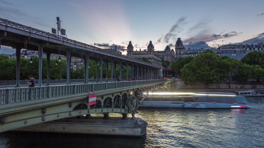 Pont de Bir-Hakeim (formerly pont de Passy) day to night transition timelapse - a bridge that crosses the Seine River. Central arch decorated with monumental statues. Cars and trains traffic on road | Shutterstock HD Video #1070795434