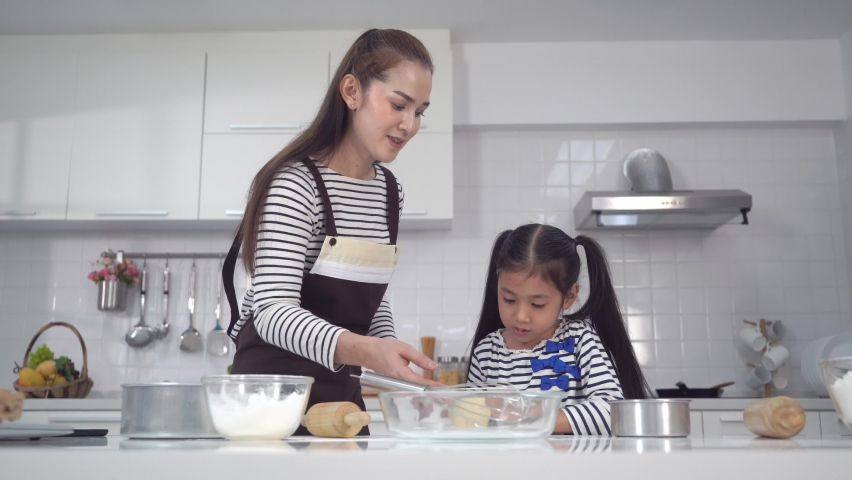 Asian Mother and Child is having a happy time cooking bakery in home kitchen | Shutterstock HD Video #1070795551