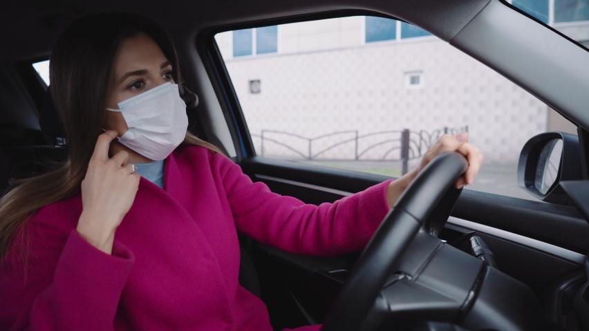 The girl takes off her mask in the car and smiles with relief | Shutterstock HD Video #1070795920