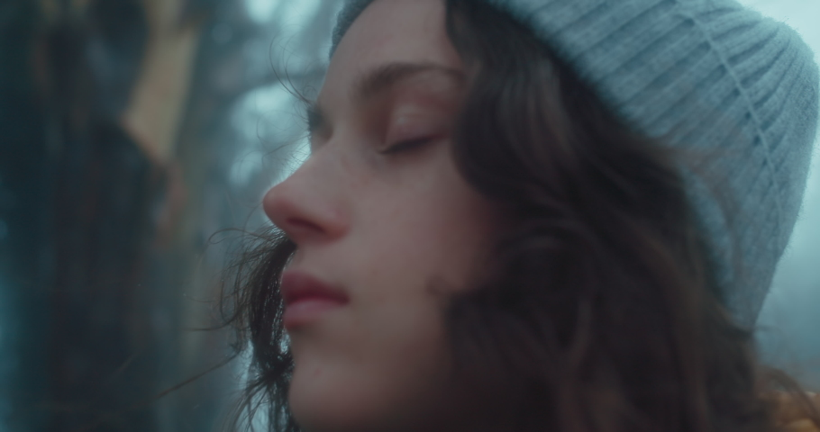 Beautiful calm young woman look up at sky in forest, close her eyes and breathe in fresh clean mountain air. Vacation away from city, mindfulness and inner life. Disconnect from everyday life | Shutterstock HD Video #1070796478