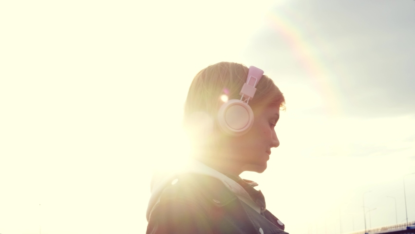 Young caucasian girl in headphones, light sweatshirt and black leather twist close-up in city. Spectacular setting sun, beautiful rays. The concept of happiness, music, freedom, walks. | Shutterstock HD Video #1070796949