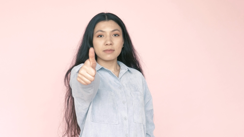 Serious concentrated latin hispanic brunette woman showing thumbs up, like gesture with fingers, satisfied with service, recommendation. Indoor studio shot isolated on pink background | Shutterstock HD Video #1070797177