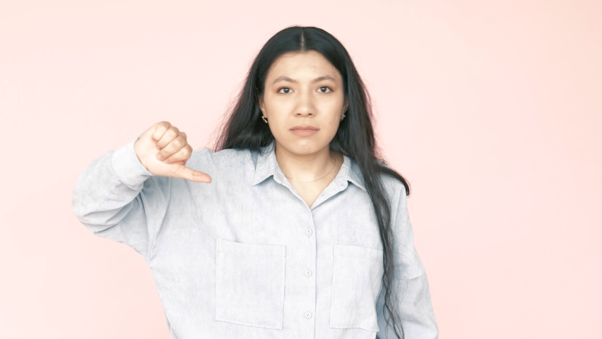 No no no! Young adult brunette woman pointing on herself, warning with finger, saying no, be careful, scolding and giving advice to avoid danger. Indoor studio shot isolated on pink background. | Shutterstock HD Video #1070798026