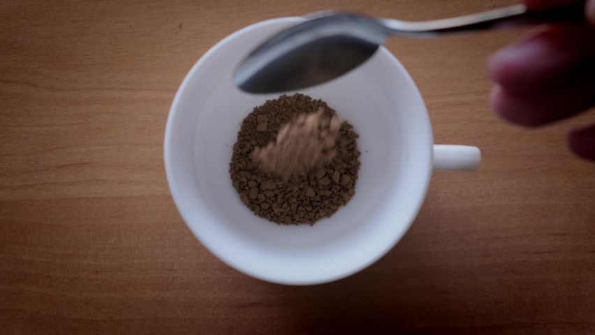 Granules of instant coffee are poured into a white cup. slow motion, Top view   Shutterstock HD Video #1070798101