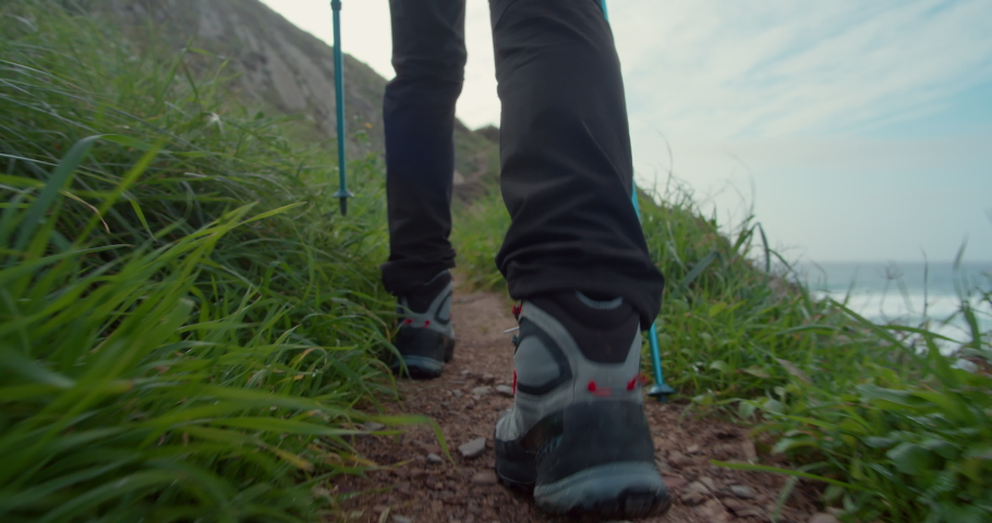 Low angle camera follows person in hiking boots with walking sticks walk on narrow hiking path. Man or woman on hike trail on mountain edge. Soles of shoes step by step, hiking to success | Shutterstock HD Video #1070799871