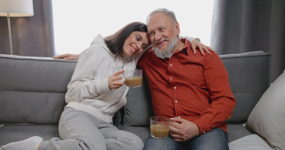 Smiling grown up daughter communicating with old 80s father, sitting together on comfortable couch at home with cups of hot tea. Happy young woman talking how things are with elder retired granddaddy.