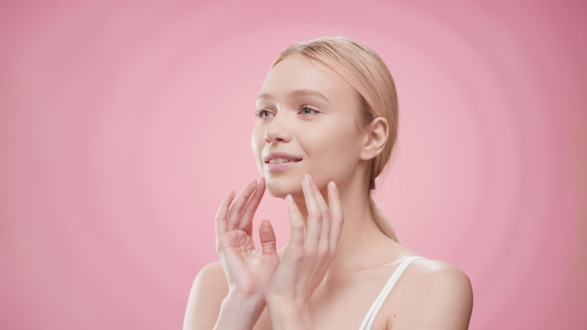 Young slim pretty blonde Caucasian woman in white bikini touches her face and turns her head looking at the camera against pink ripple water background | Moisturizing cream commercial