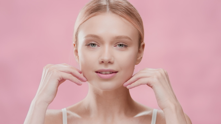 Young slim gorgeous blond European woman in white bikini opens her eyes moving her head up and touching her face against pink ripple background | Face skin care commercial