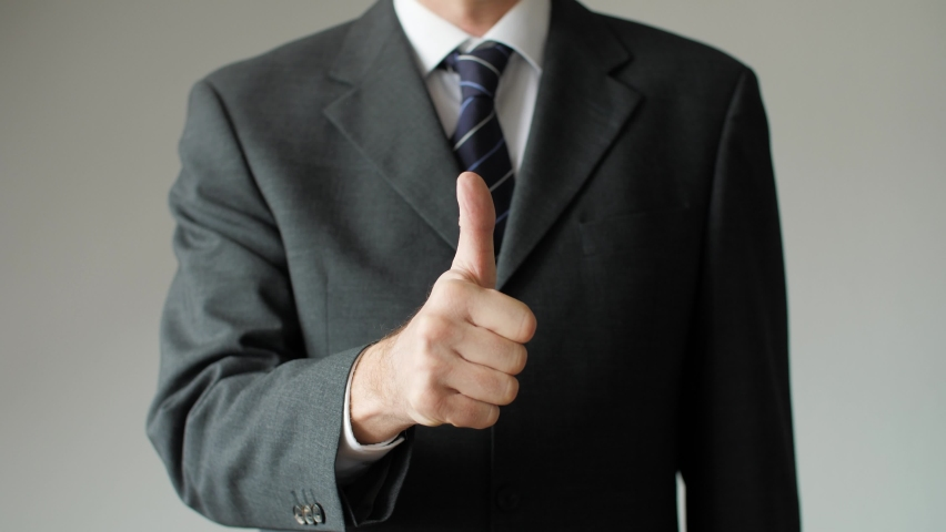 Close up of successful business man giving a thumbs up showing approval. Businessman, boss, and entrepreneur with positive gesture signaling OK, all right, and satisfaction.
