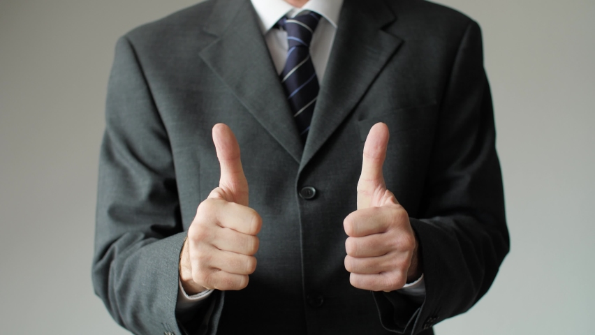 Close up of successful business man giving two thumbs up showing approval. Businessman, boss, and entrepreneur with positive gesture signaling OK, all right, and satisfaction.