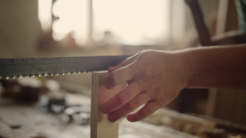 Unrecognized wood worker sawing wooden plank in carpentry workshop in slow motion. Closeup unknown man using saw in studio. Male hands producing wooden product indoors. Royalty-Free Stock Footage #1070833279