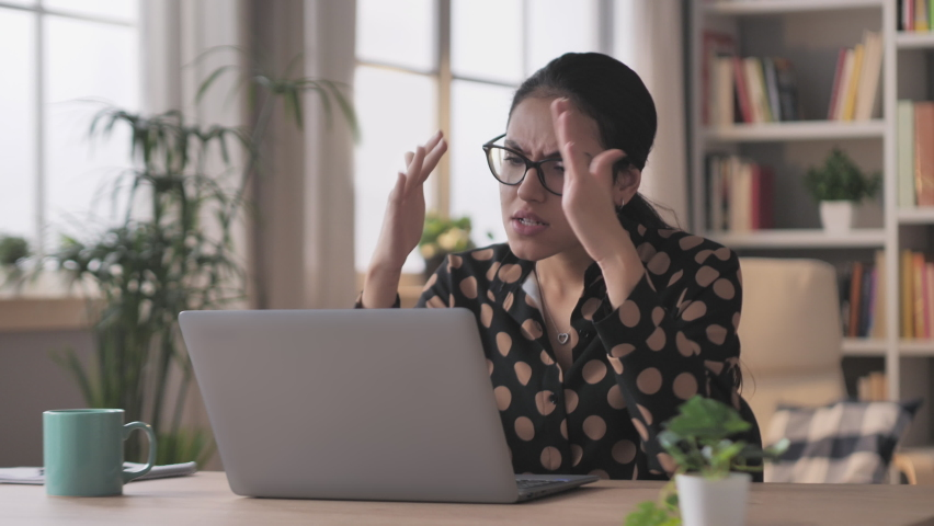 angry business woman sits at the desk works from home at the laptop burst in rage,arab female businesswoman working at the computer feels furious stressed,having problems at work Royalty-Free Stock Footage #1070854891