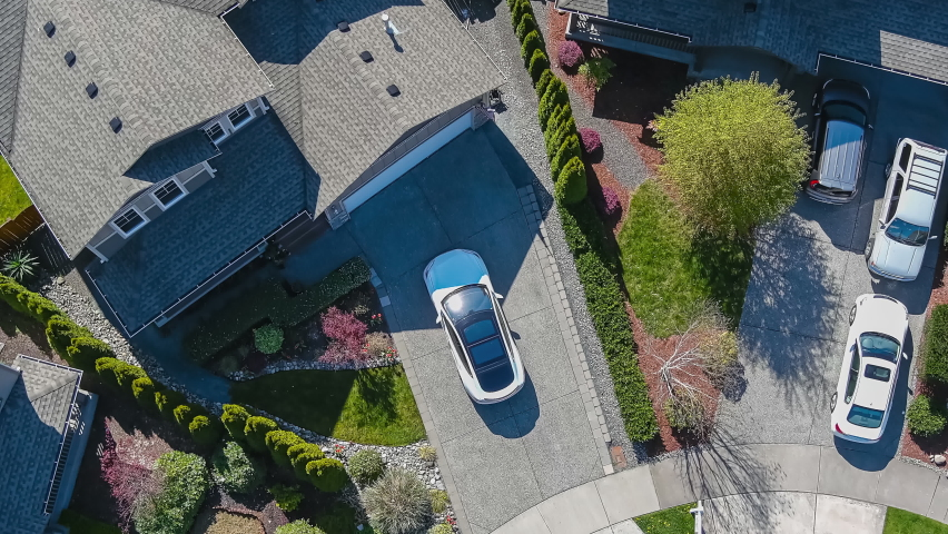 Aerial view of a white car driving through a suburban neighborhood arriving at home; drone follow shot