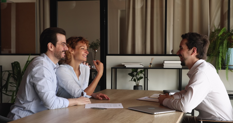 Side view smiling young family couple signing contract with professional hispanic realtor, celebrating making deal or purchasing first own apartment, taking keys from dwelling at meeting in office. Royalty-Free Stock Footage #1070896525