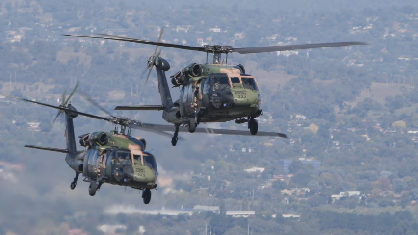CANBERRA, AUSTRALIA - MARCH, 31, 2021: slow motion tracking clip of two black hawk helicopters approaching during the raaf centenary flypast