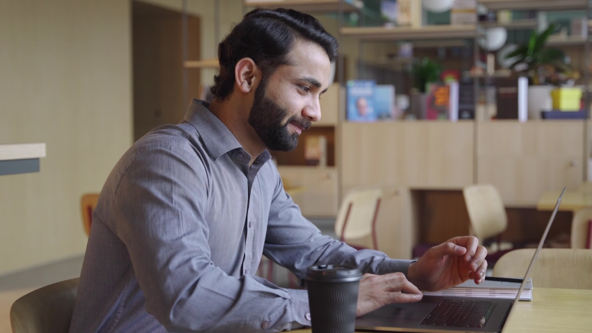 Happy bearded indian business man working on laptop from home office. Male indian executive using computer remote studying, browsing web, having virtual meeting, typing on computer. Royalty-Free Stock Footage #1070928703