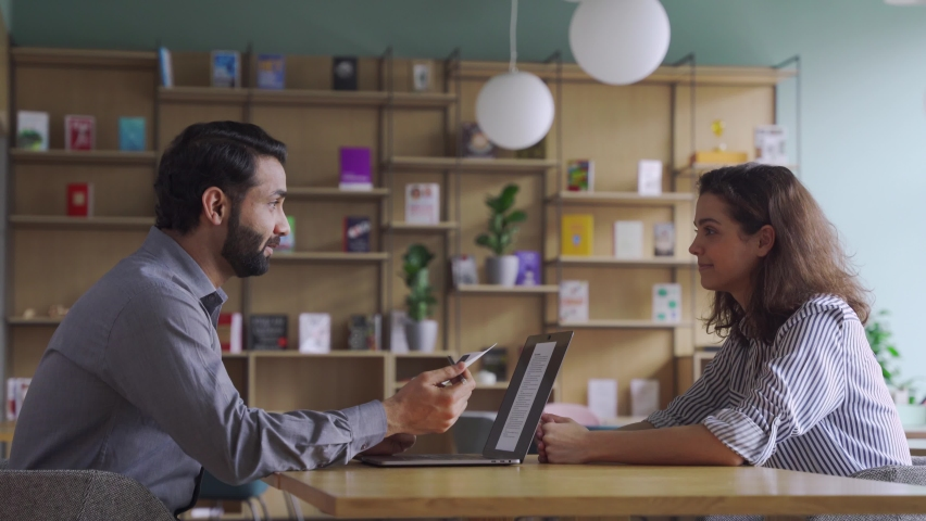 Indian male hr specialist manager, employer, boss talking to female latin candidate at job interview, consulting client at office meeting. Hiring and employment, insurance, recruitment concept. Royalty-Free Stock Footage #1070928715