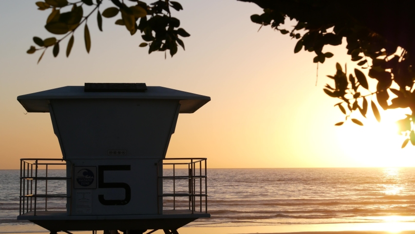 Lifeguard watch tower, sunny sunset beach, Oceanside USA. Rescue station, waterfront watchtower hut and tree leaves, pacific ocean coast atmosphere. California summertime aesthetic, Los Angeles vibes. | Shutterstock HD Video #1070930953
