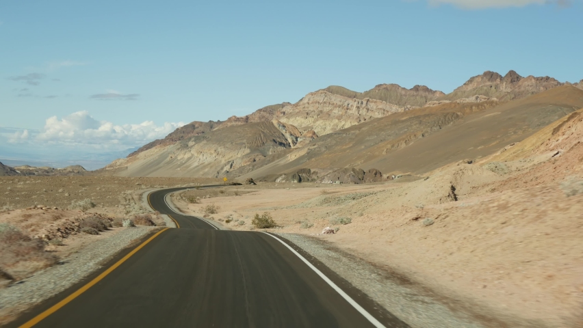 Road trip to Death Valley, Artists Palette drive, California USA. Hitchhiking auto traveling in America. Highway, colorful bare mountains and arid climate wilderness. View from car. Journey to Nevada. | Shutterstock HD Video #1070930995