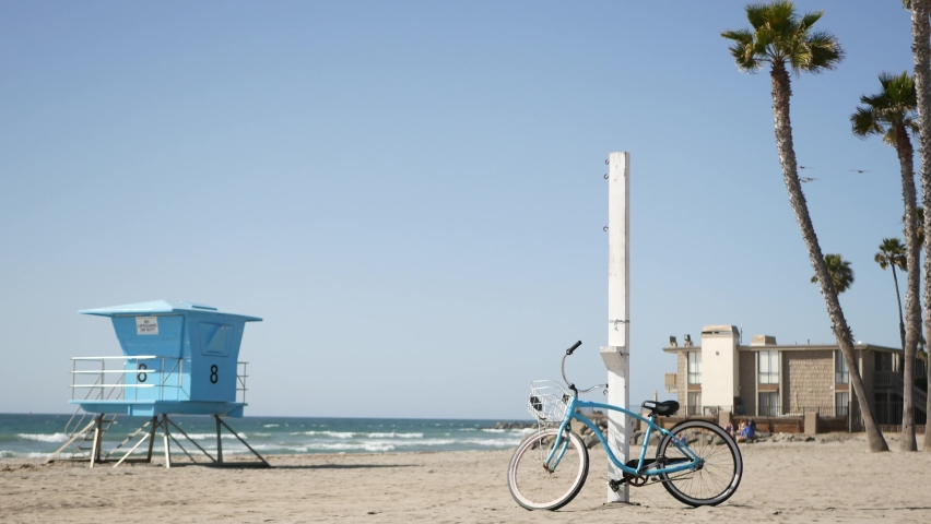 Blue bicycle, cruiser bike by ocean beach, pacific coast, Oceanside California USA. Summertime vacations, sea shore. Vintage cycle on sand near lifeguard tower or watchtower hut. Sky and water waves. | Shutterstock HD Video #1070931052