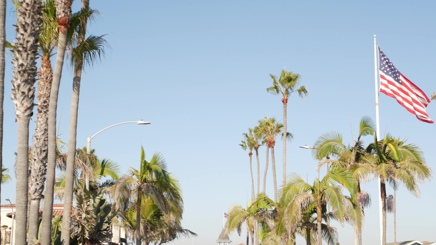 Palms and american flag, Los Angeles, California USA. Summertime aesthetic of Santa Monica Venice Beach. Star-Spangled Banner, Stars and Stripes. Atmosphere of patriotism in Hollywood. LA vibes. | Shutterstock HD Video #1070931058