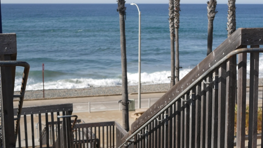 Wooden stairs, beach access in Oceanside, California USA. Coastal stairway, pacific ocean waves and palm trees. Vacations by sea in United States. Sunny tropical day, summertime aesthetic. Staircase. | Shutterstock HD Video #1070931064