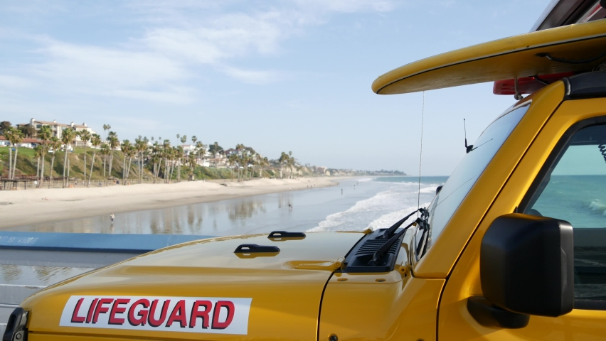 Yellow lifeguard car, San Clemente beach pier, California USA. Coastline rescue life guard pick up truck, lifesavers vehicle. Auto and ocean coast. Los Angeles vibes, summertime aesthetic atmosphere. | Shutterstock HD Video #1070931067