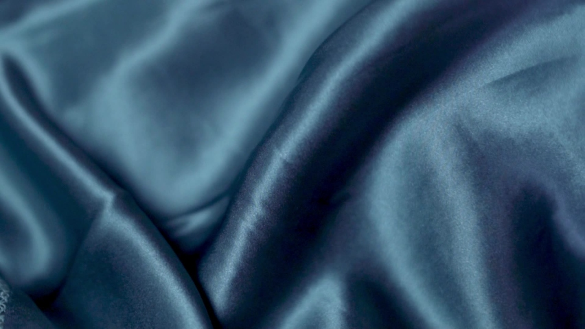 Smooth Natural Shiny Blue Silk Fabric, Smooth Silk Texture Of Fashion Clothes, Underwear, Close-up. Blue Shiny Silk Material. Clothing Factory. Textile Industry. Abstract Background of Silk Fabric. Royalty-Free Stock Footage #1070931934