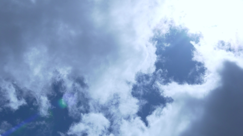 Beautiful Time Lapse of White and Gray Clouds of the Sun with Rays and Highlights in the Blue Sky. Cloudy Weather on A Sunny Summer Day. Background of Sun Clouds and Sky. Fresh Air, Layer, Atmosphere.