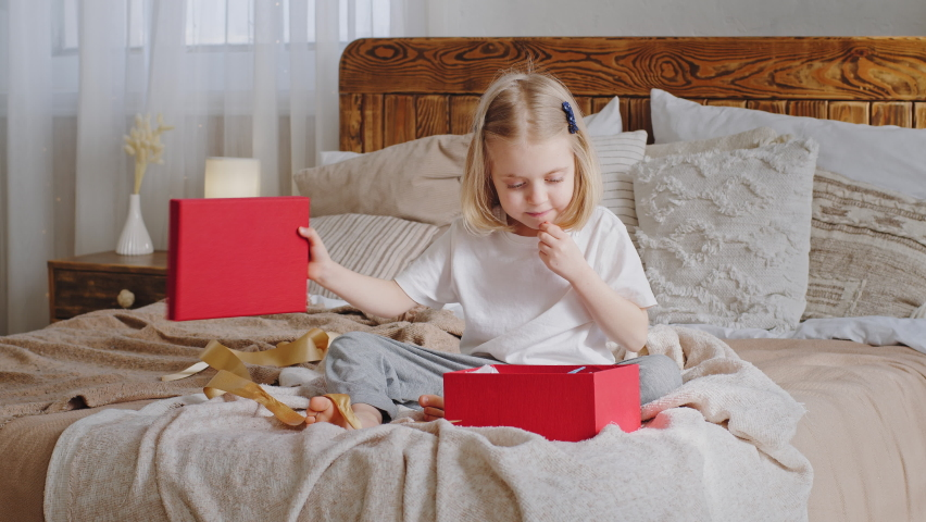 Curious little girl happy preschooler blonde daughter cute baby kid child sitting on cozy bed with festive red gift box unpacks present unties yellow ribbon looks inside, home holiday birthday party Royalty-Free Stock Footage #1070947201