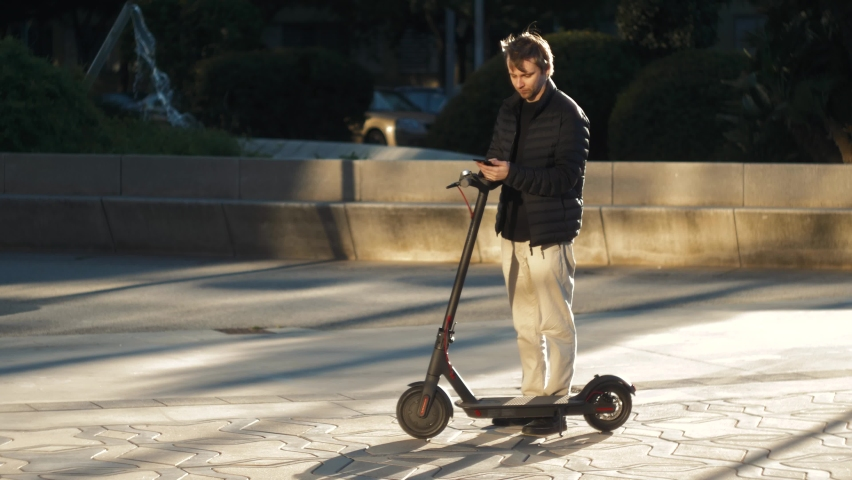 Tourist man take Electric Kick scooter or bike bicycle in sharing parking lot, tourist phone application. New sharing rent business project started in city, eco transportation | Shutterstock HD Video #1070948248