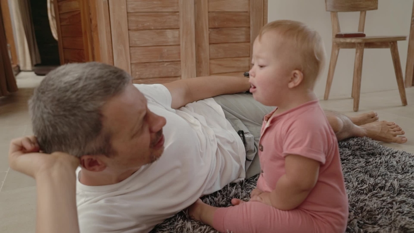Happy toddler girl down syndrome play with her father at home. Baby shows her daddy funny and emotional grimaces and gestures. Royalty-Free Stock Footage #1070950693