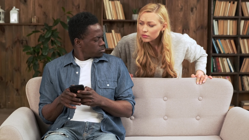 Cheater man dating online with a smart phone and girlfriend is spying sitting on a sofa at home. Mixed race ethnicity couple Royalty-Free Stock Footage #1070955313