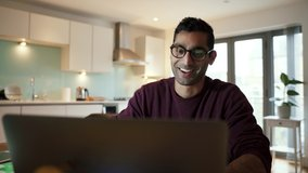 Mixed race business man working from home waving while on video call using laptop