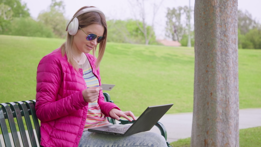 Female shopper using instant easy mobile payments making purchase in online store. Smiling young woman customer holding credit card and laptop sitting on bench in green park. RED HELIUM footage 8K Royalty-Free Stock Footage #1070972143