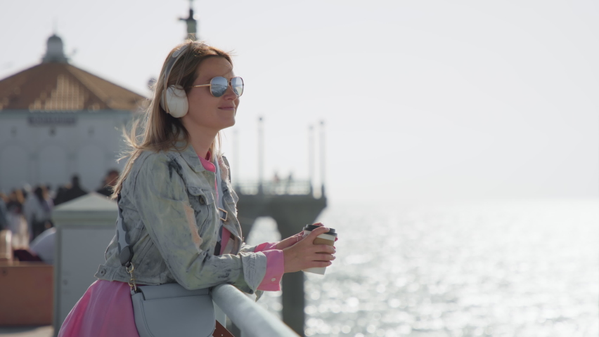 Slow motion 8K footage of happy people with ocean background. Cinematic shot on RED Helium camera. Stylish woman in pink dress drinking coffee on ocean pier and enjoying beautiful summer outdoors | Shutterstock HD Video #1070972152